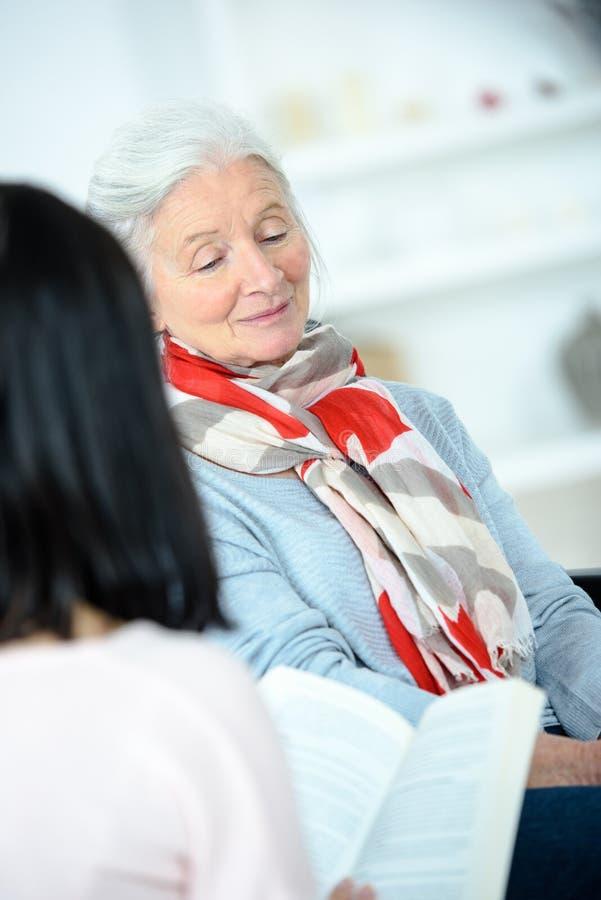 Junge weibliche Lesung zur älteren Frau zu Hause lizenzfreie stockfotografie