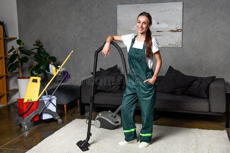 junge weibliche Reinigungsfirmenarbeitskraft, die am Staubsauger und dem Lächeln sich lehnt stockfoto