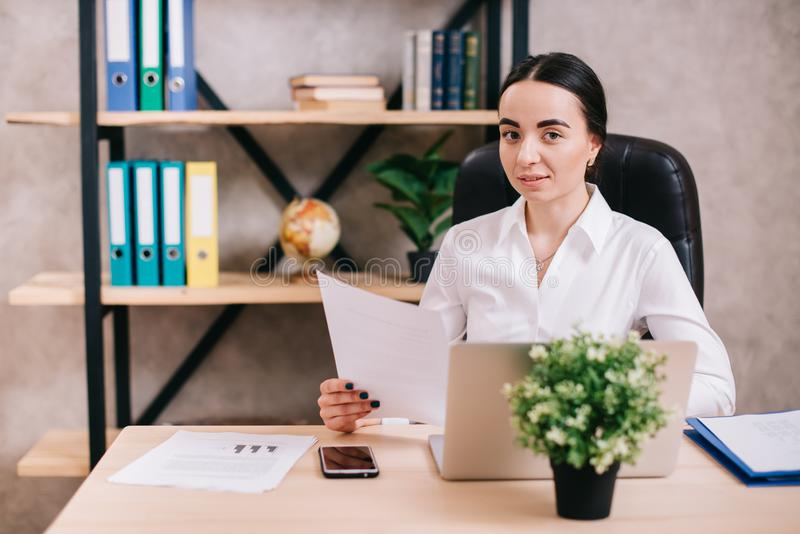 Junge weibliche schauende Kamera im Büro stockfotografie