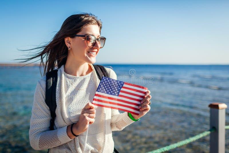 Junge weibliche touristische bewundern Landschaft von Rotem Meer und von Halten von USA-Flagge auf Pier Unabh?ngigkeitstag von Am stockbild