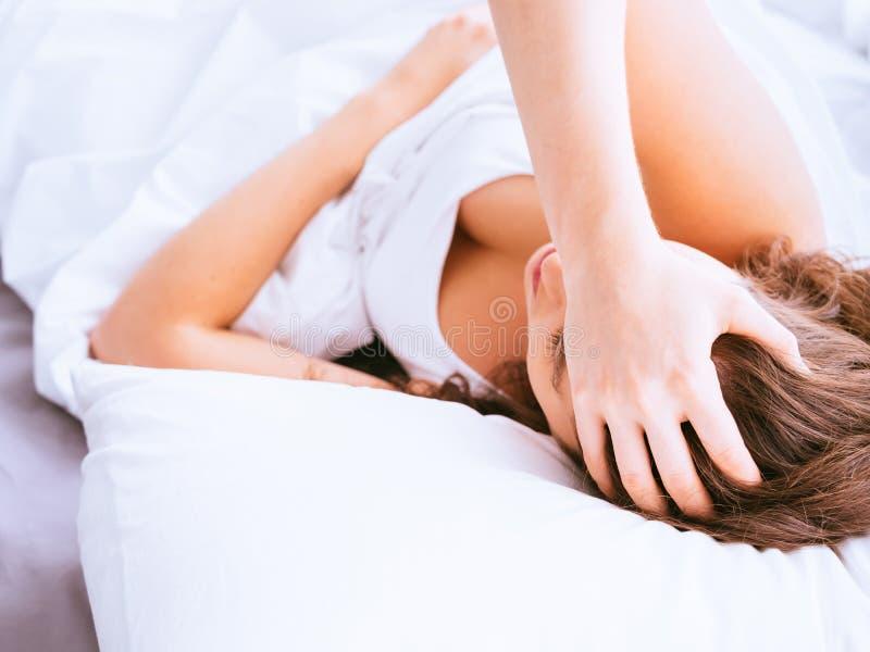 Junge, welche die kaukasische Frau hat Migräne und Kopfschmerzen wegen der Schlafenprobleme oder -schlaflosigkeit erleiden lizenzfreies stockfoto