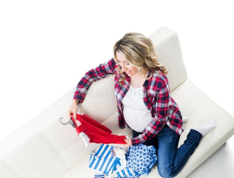 Junge werdende Mutter gekauft Kinderkleidung stockfoto