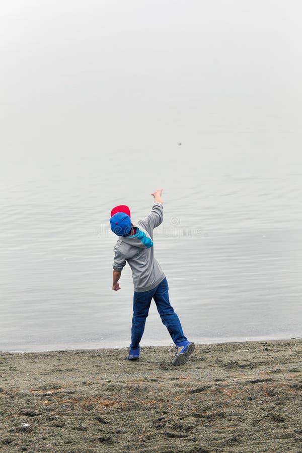 Junge wirft Felsen im Wasser lizenzfreies stockbild
