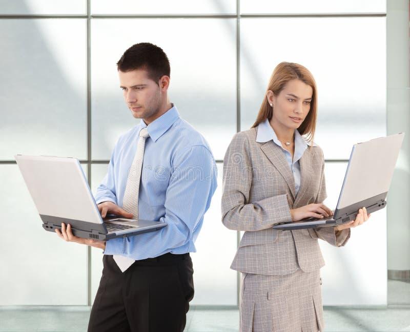 Junge Wirtschaftler, die Laptop in der Bürovorhalle verwenden lizenzfreie stockfotos