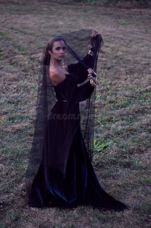 Junge Witwe, die schwarzen Schleier trägt stockbild