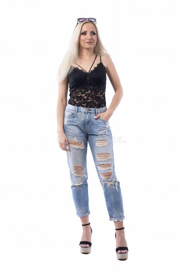 Junge wunderschöne Blonde-Frau mit Sonnenbrille auf Kopf und Hand in Tasche, die interessiert aussieht lizenzfreie stockbilder