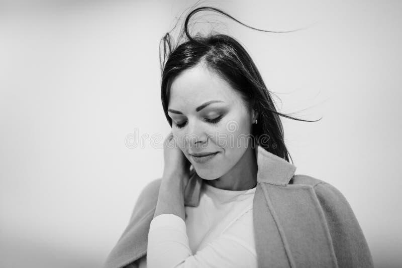 Junge zarte lächelnde Brunettefrau mit ihren Augen geschlossen im hellen Mantel auf Stadtweg Der Wind brennt ihr Haar durch Schwa stockfotos