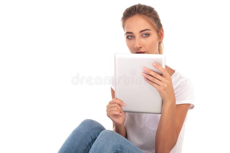 Junge zufällige Frau, die eine Tablette über ihrem Gesicht hält lizenzfreie stockfotografie