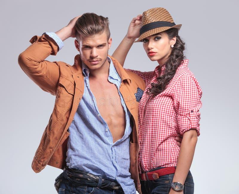 Junge zufällige Paare, die auf Studiohintergrund aufwerfen lizenzfreie stockfotos