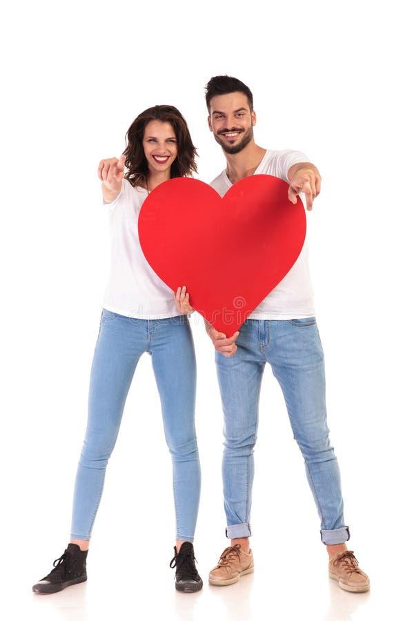 Junge zufällige Paare, die ein großes Herz und Punktfinger halten stockfotos