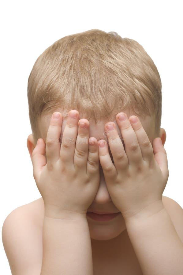 Junge, zum des Gesichtes hinter Händen zu verstecken lizenzfreie stockfotos