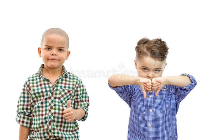 Junge zwei mit den Daumen den oben und Daumen unten auf weißem lokalisiertem backround stockfotos