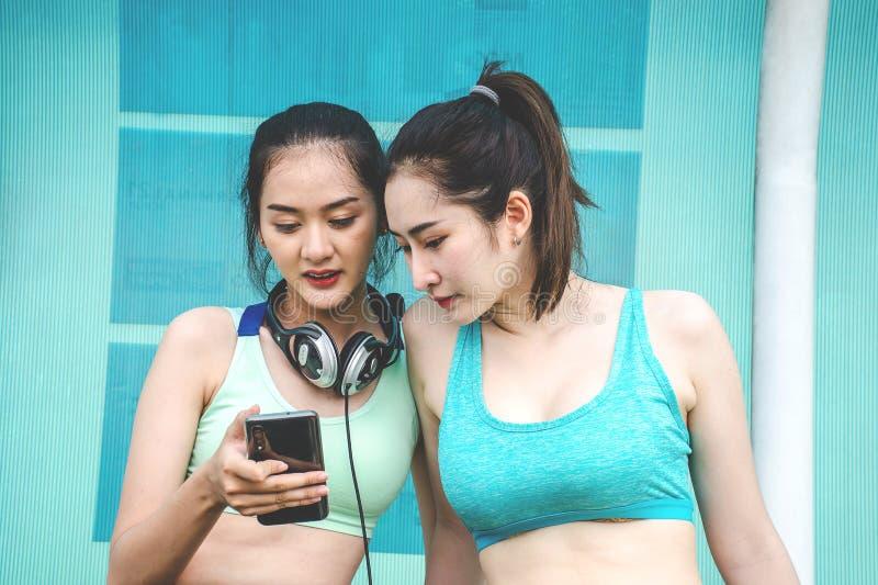 Junge zwei Sportfreundinnen in der Sportkleidung sitzen auf Bank, sich entspannen nach Sporttraining lizenzfreie stockbilder