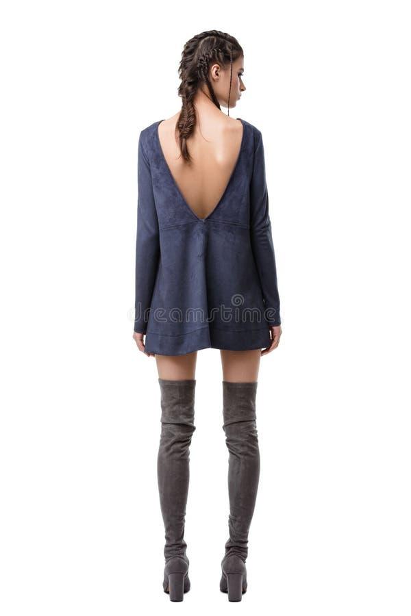Jungedame von der Rückseite im dunkelblauen Velourslederkleid mit Schnitt auf Rückseiten- und Kniestiefeln lokalisierte lizenzfreie stockfotografie