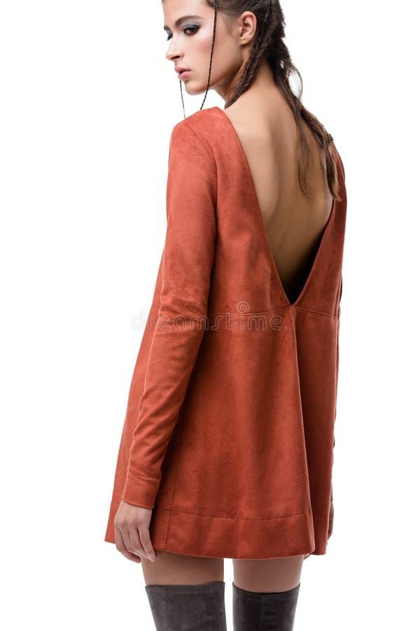 Jungedame von der Rückseite im Ingwervelourslederkleid mit Schnitt auf Rückseiten- und Kniestiefeln auf weißem Hintergrund lizenzfreies stockbild
