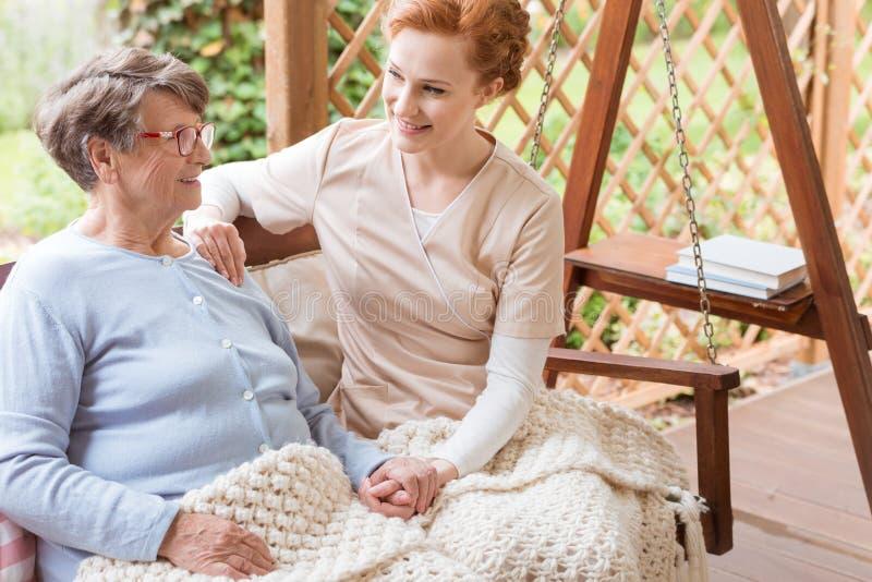 Jungefreiwilliger und eine ältere Frau, die zusammen auf einem Garten sitzt lizenzfreie stockfotos