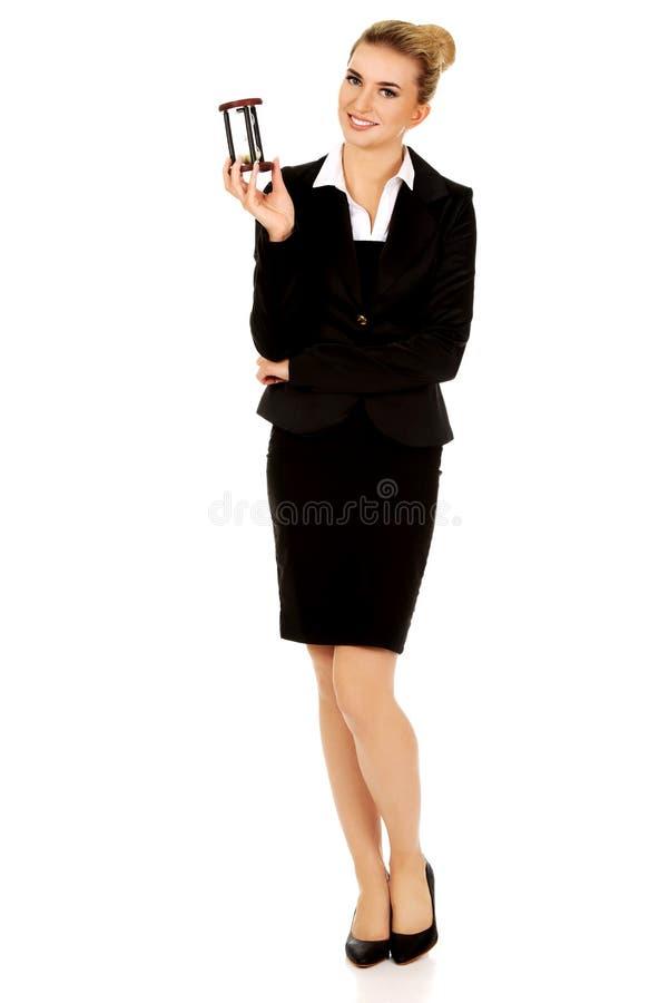 Jungelächelngeschäftsfrau mit Sanduhr - setzen Sie Zeit Konzeptes fest stockbild