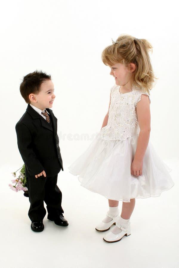 Jungen-überraschendes Mädchen mit Blumen lizenzfreie stockfotos