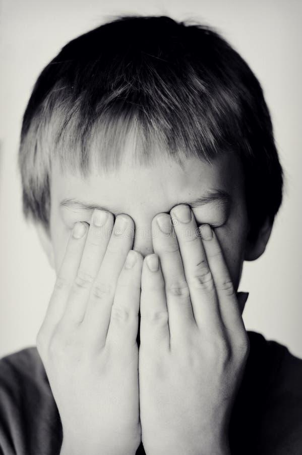 Jungen-Bedeckungs-Augen mit den Händen stockbilder