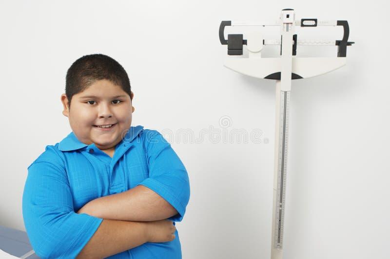 Jungen-bereitstehende wiegende Skala in der Klinik lizenzfreies stockfoto