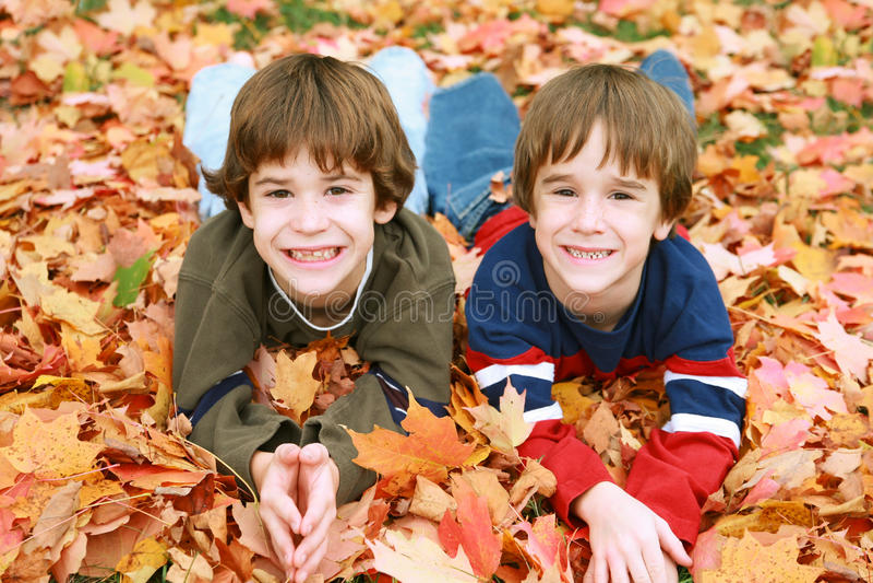 Jungen in den Blättern stockfoto