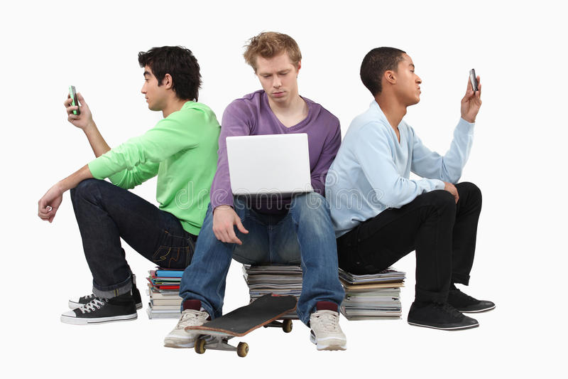 Jungen, die auf Büchern sitzen stockbilder