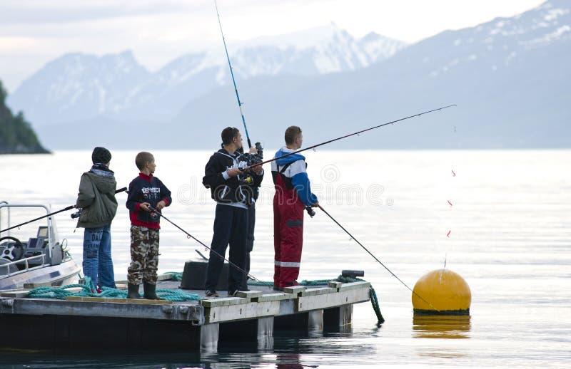 Jungen, die auf Fjord fischen stockfoto