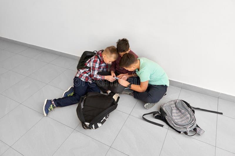 Jungen, die auf Schulkorridor sitzen und zusammen spielen lizenzfreies stockfoto
