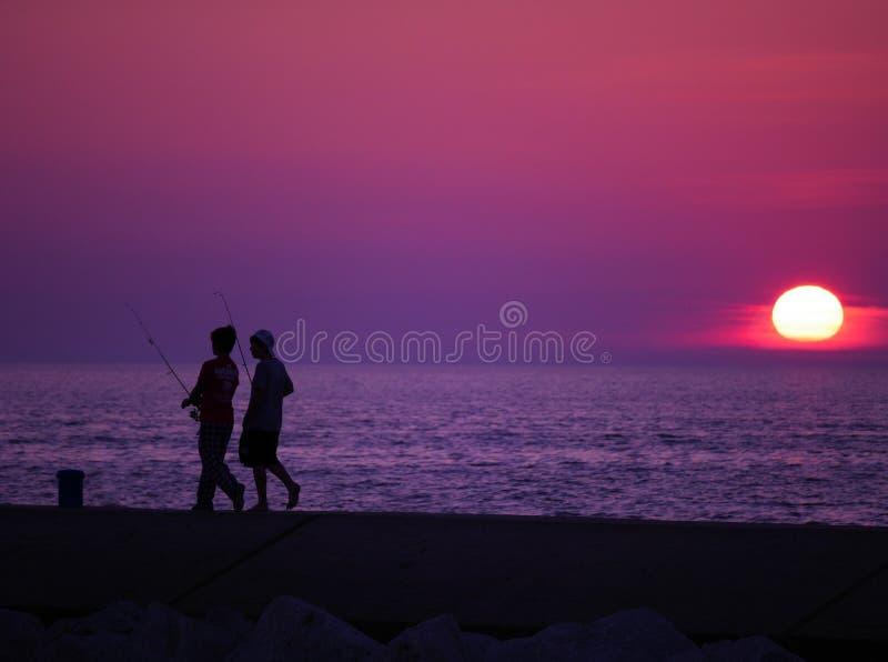 Jungen, die bei Sonnenuntergang fischen lizenzfreies stockbild