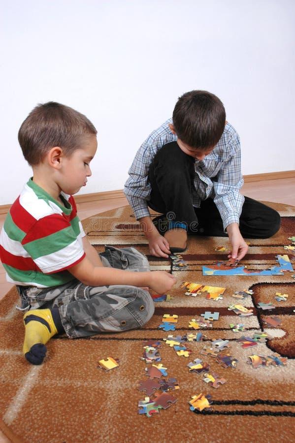 Jungen, die das Puzzlespiel spielen lizenzfreie stockbilder