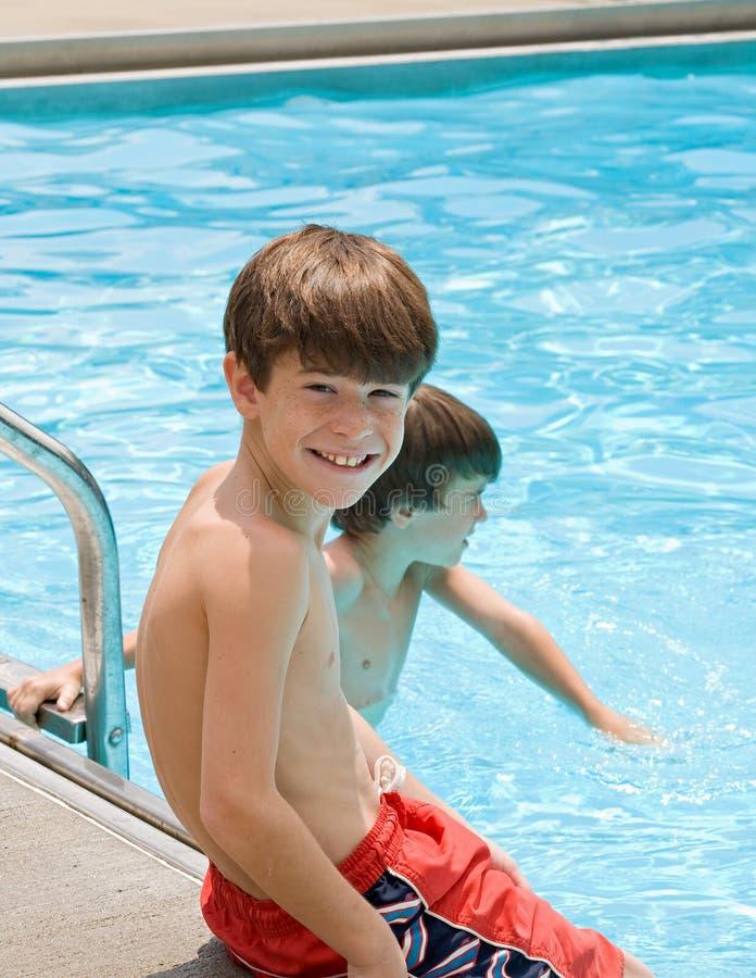 Jungen, die eine Spaß-Zeit am Pool haben lizenzfreie stockfotografie