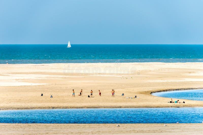 Jungen, die Fußball auf dem Strand spielen lizenzfreie stockfotos