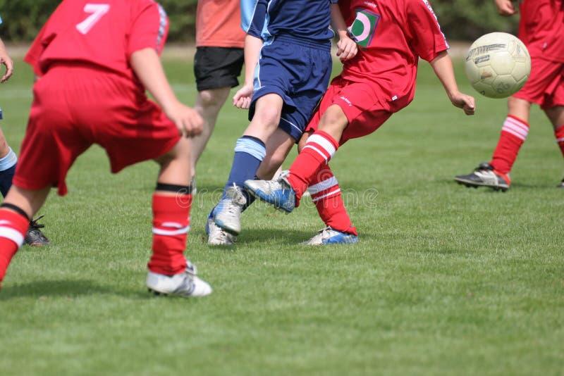 Jungen, die Fußball spielen lizenzfreie stockfotos