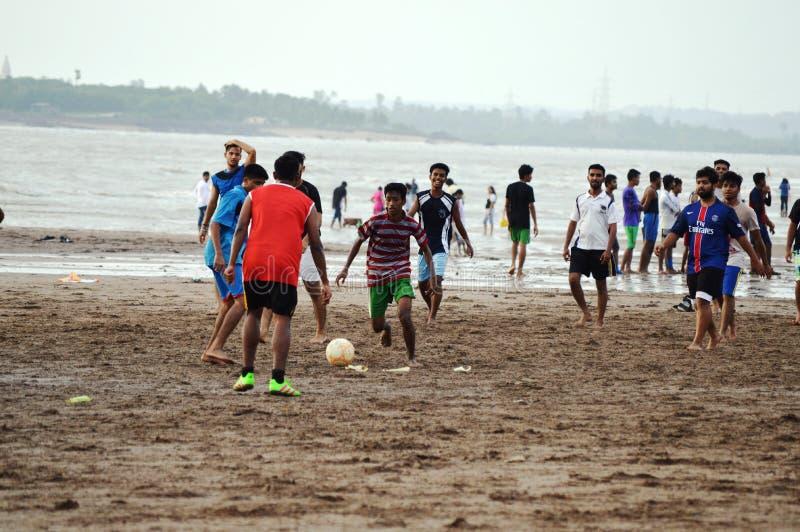 Jungen, die Fußball am Strand spielen stockfoto