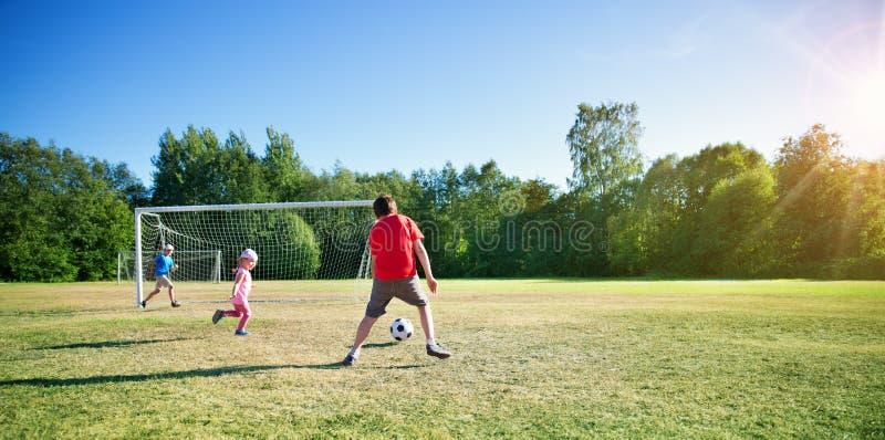 Jungen, die Fu?ball auf dem Feld mit Toren spielen stockbilder