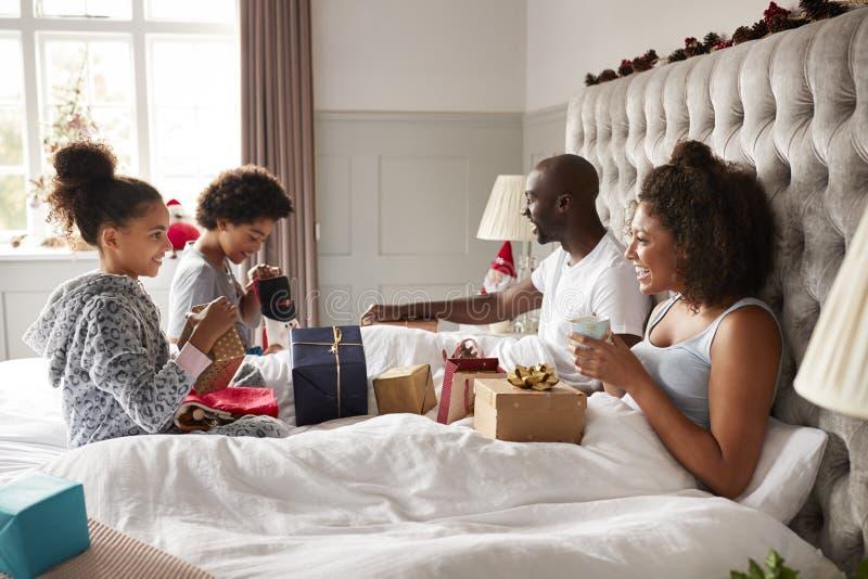 Jungen, die Geschenke auf parentsï ¿ ½ Bett auf Weihnachtsmorgen öffnen, während ihre Eltern oben im Bett aufpassend sitzen, Seit stockbild