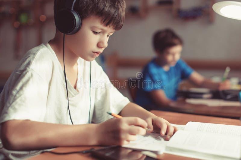 Jungen, die Hausarbeit am Schreibtisch tun lizenzfreies stockbild