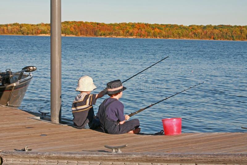 Jungen, die im Herbst fischen lizenzfreies stockbild