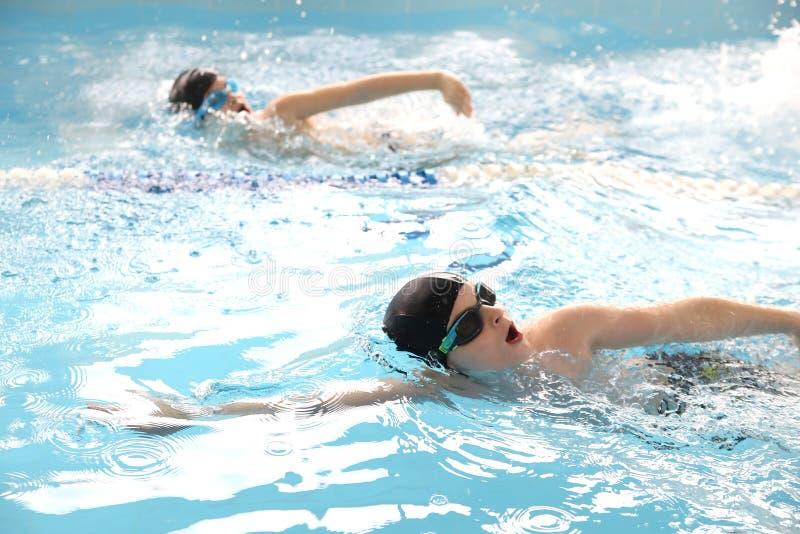 Jungen, die im Pool schwimmen lizenzfreies stockbild