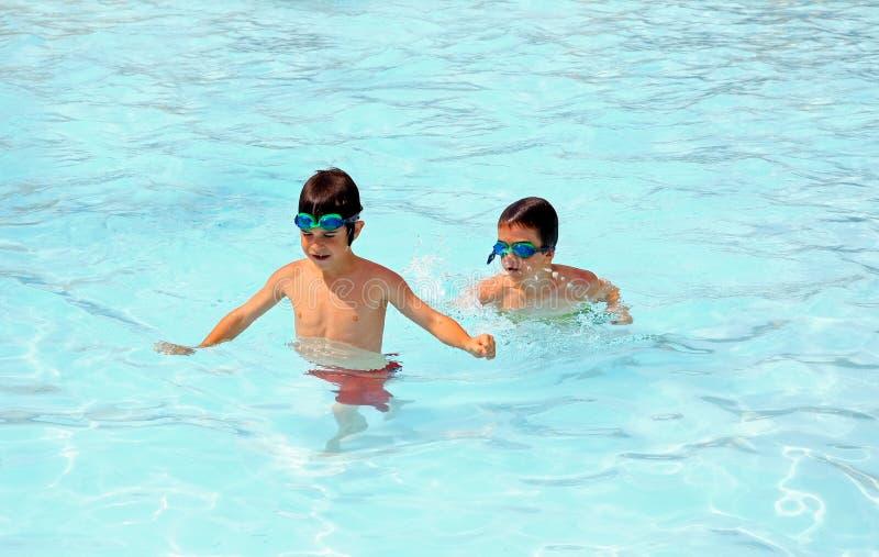 Jungen, die im Pool spielen lizenzfreie stockbilder