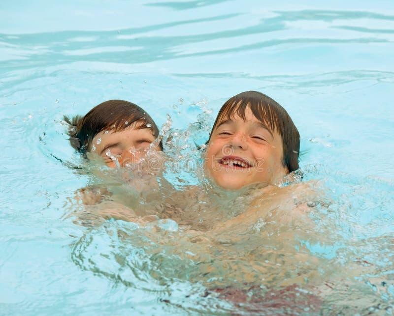 Jungen, die im Pool spielen lizenzfreies stockfoto