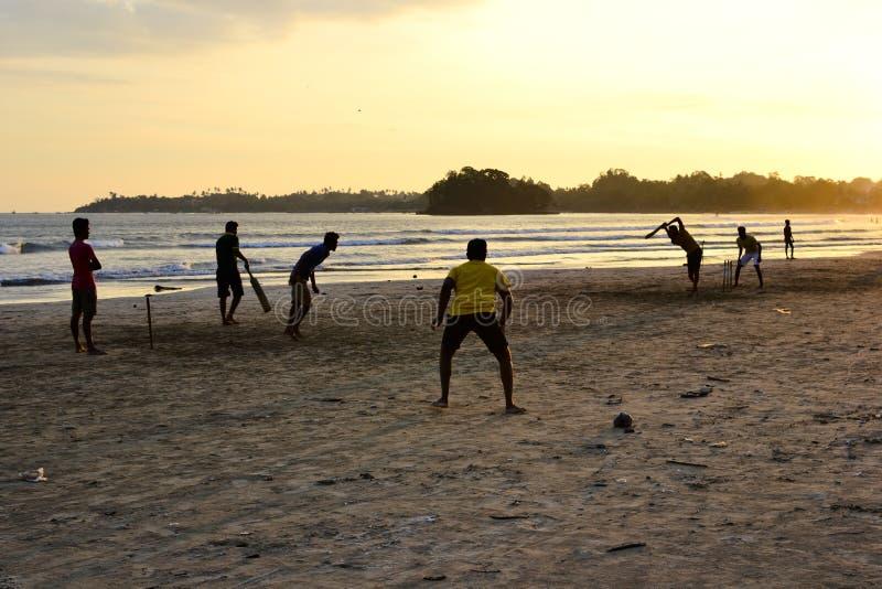 Jungen, die Kricketspiel auf einem Strand spielen stockfoto