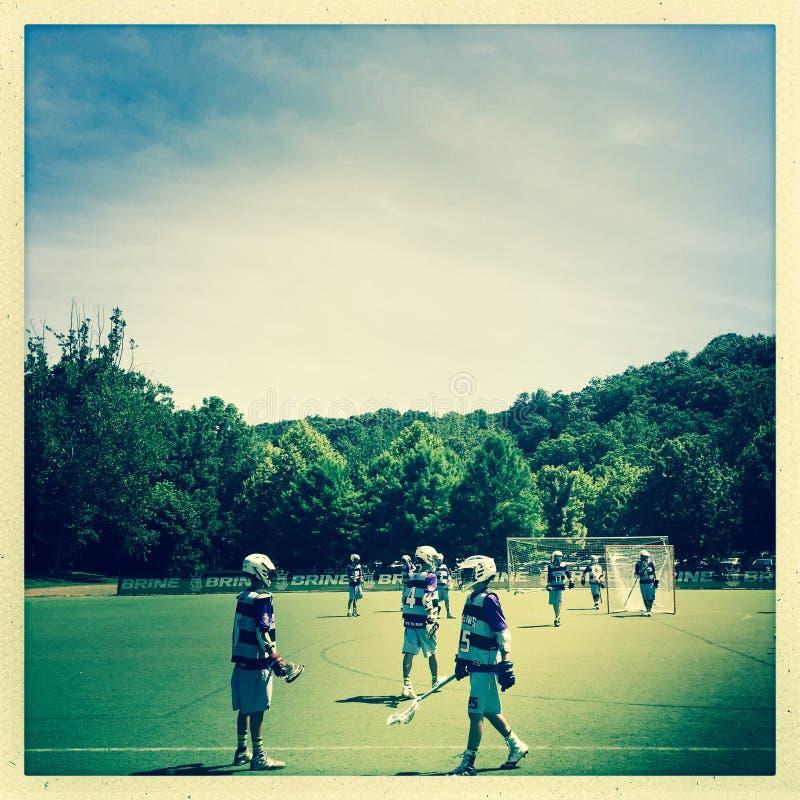 Jungen, die Lacrosse spielen lizenzfreies stockbild