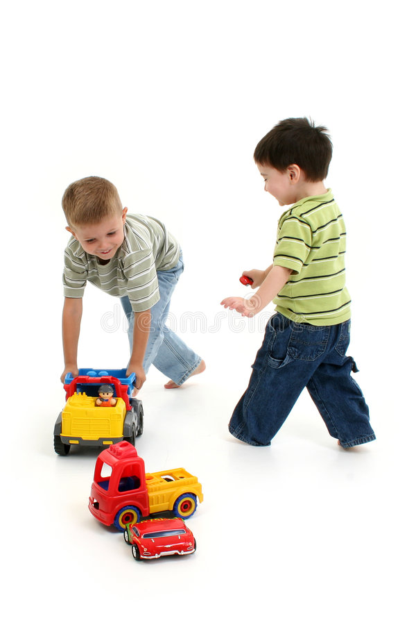 Jungen, die mit Autos und LKWas spielen lizenzfreie stockfotografie