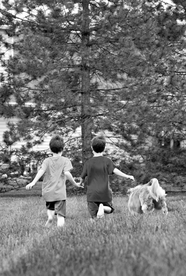 Jungen, die mit ihrem Hund laufen lizenzfreie stockbilder