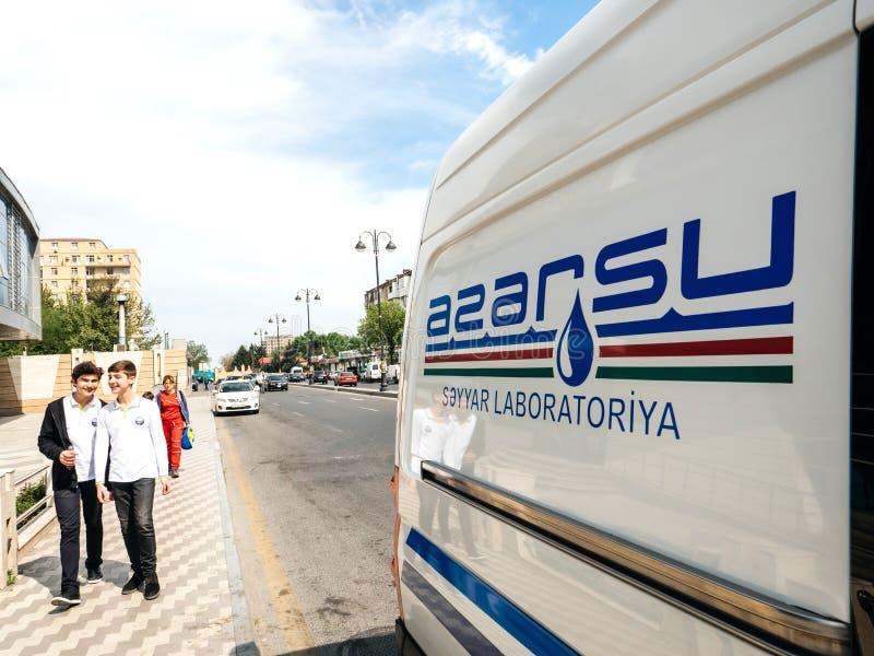 Jungen, die nahe Packwagen mit Azersu-Firmenzeichen gehen stockfoto
