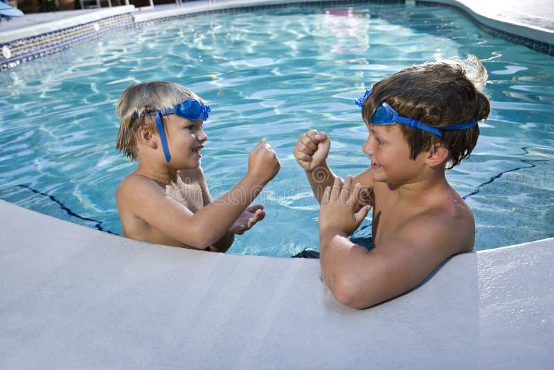 Jungen, die Spiele am Rand des Swimmingpools spielen stockfotos