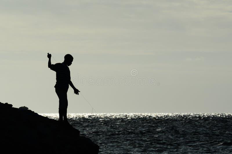 Jungen, die vom felsigen Ufer fischen stockbild