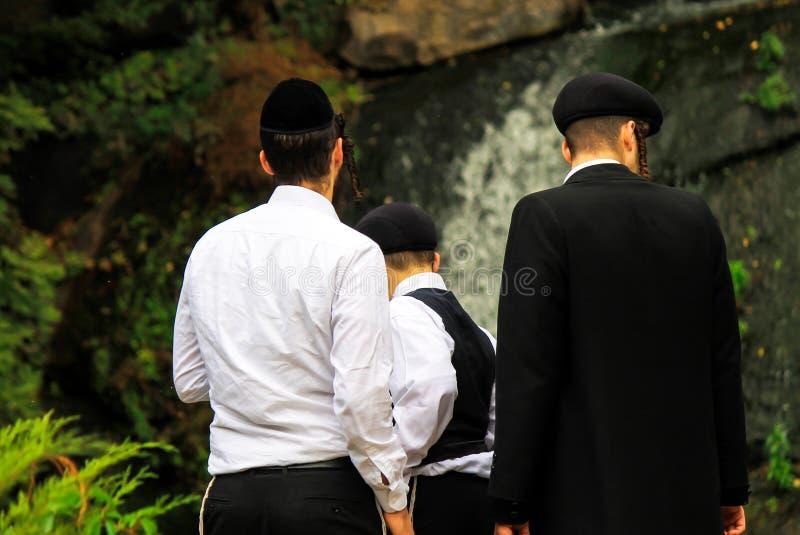 3 Jungen, eine Familie von Hasidic Juden, in der traditionellen Kleidung stehen vor einem Wasserfall im Park in Uman, Ukraine lizenzfreie stockfotografie