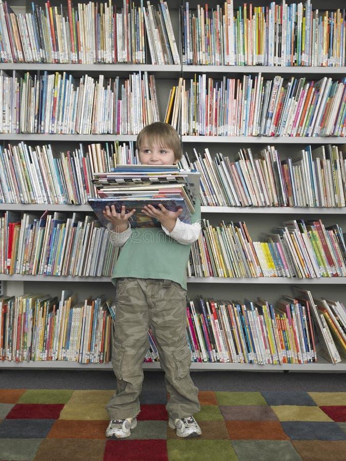 Jungen-Holding-Stapel Bücher in der Bibliothek lizenzfreie stockfotografie